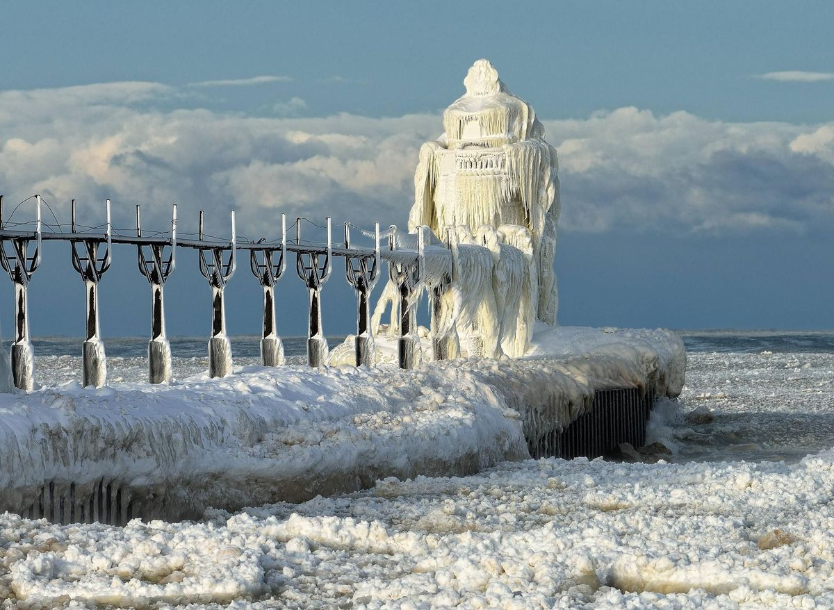A frozen lighthouse is covered in ice on a lake in St. Joseph, Michigan.