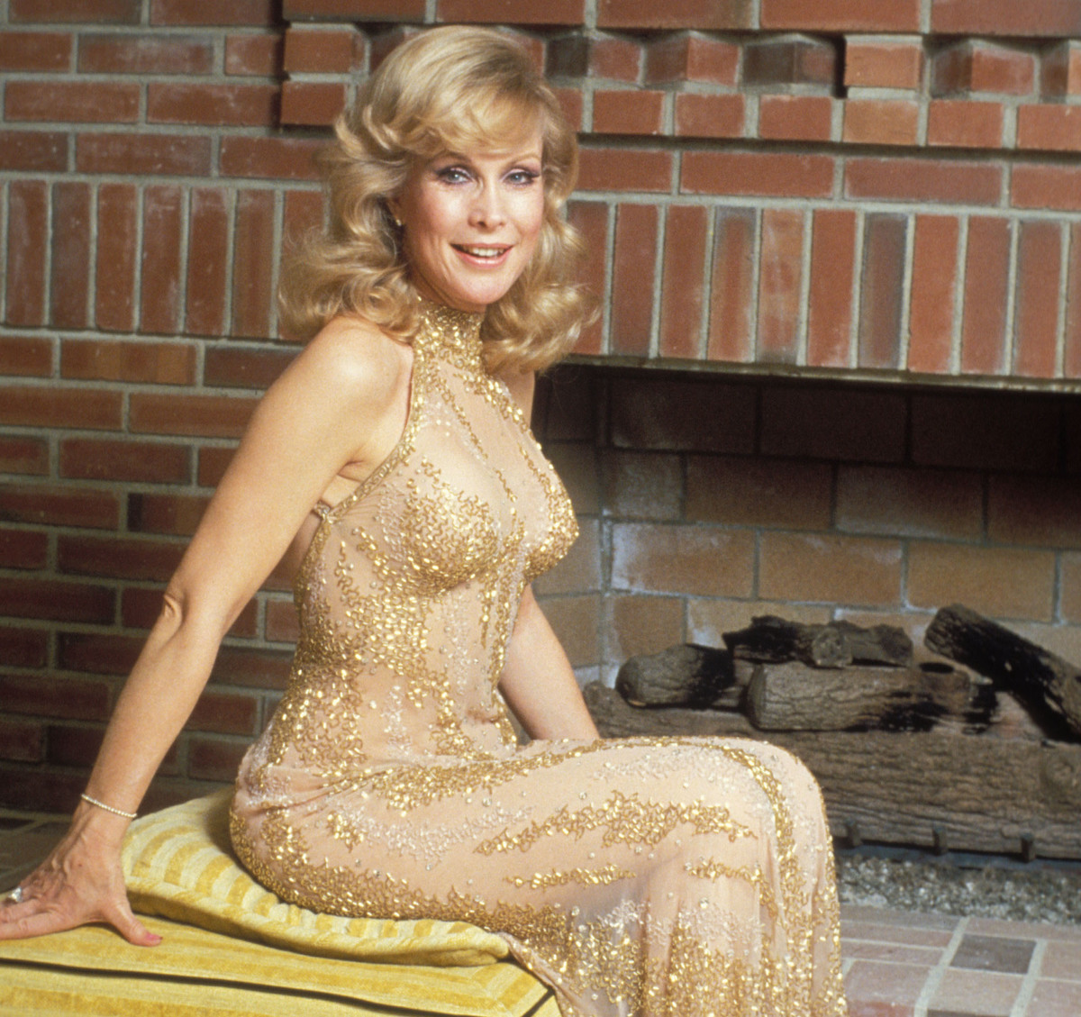 Barbara Eden sits in a golden dress in front of a fireplace.