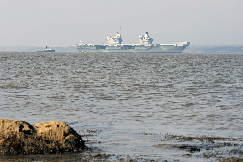 A photo from the shore shows the HMS Queen Elizabeth in the distance.