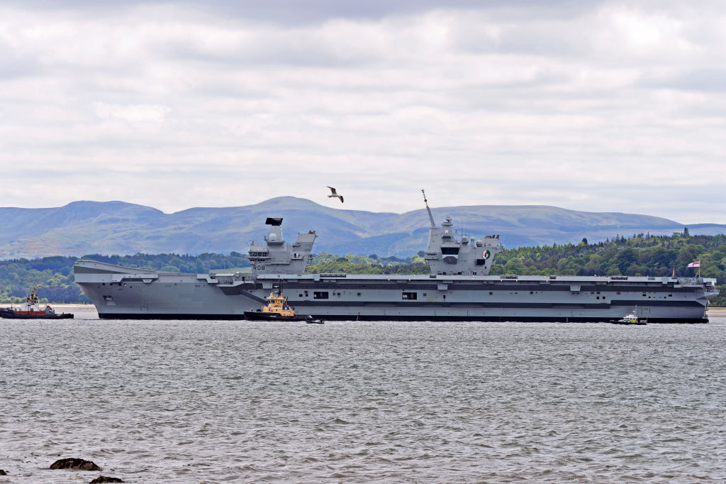 A bird flies over the HMS Queen Elizabeth as she sets sail.