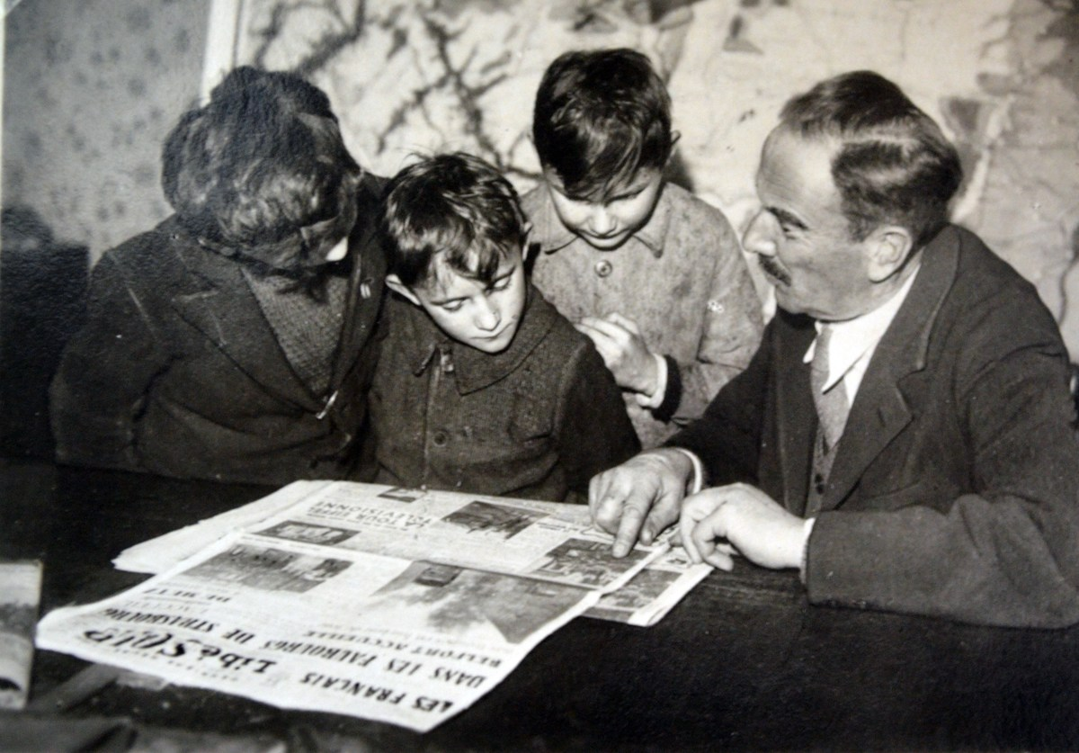 French family reads newspaper outlining the liberation of towns in Alsace Lorraine 1944.