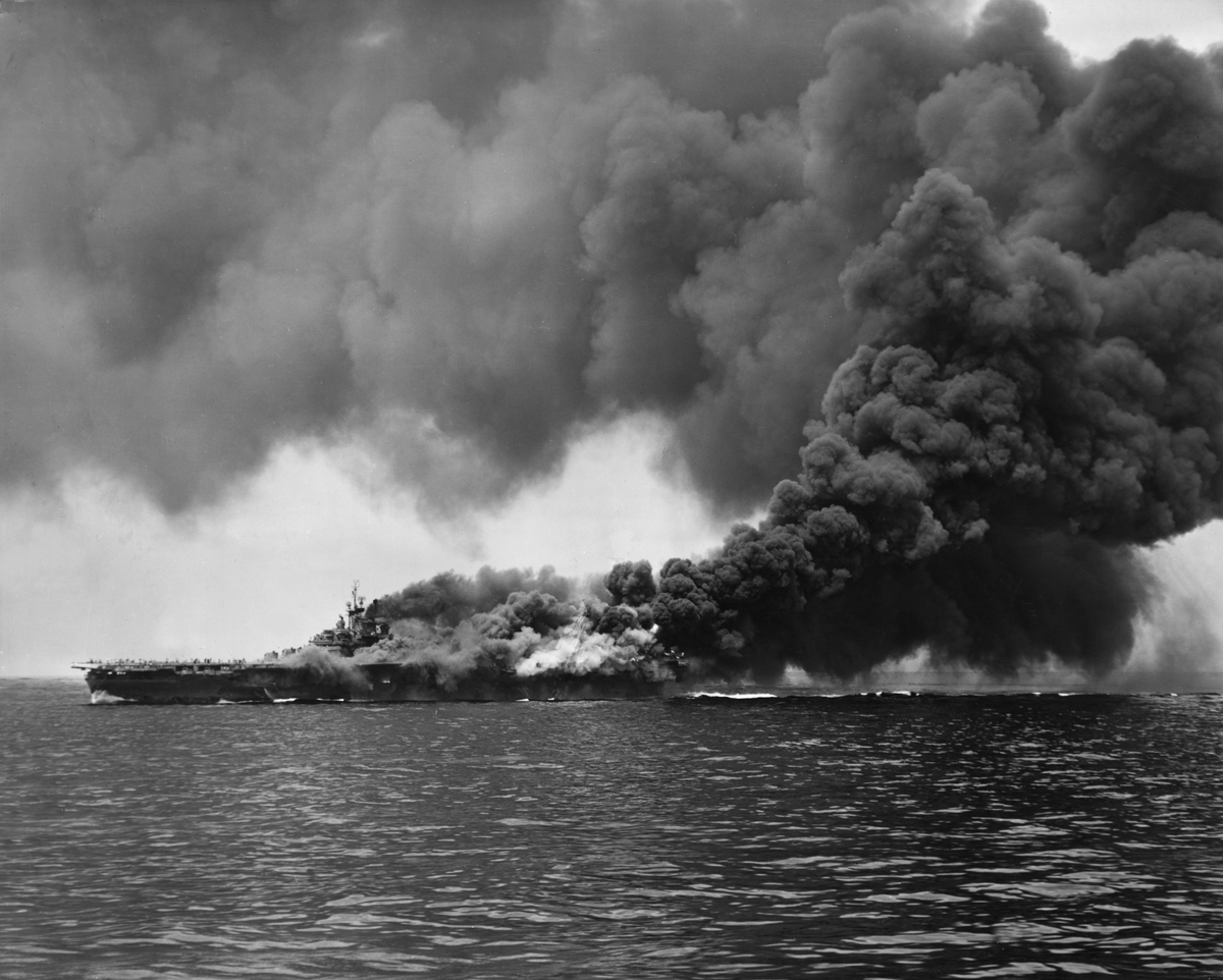 Clouds of black smoke rise from the USS 'Bunker Hill' aircraft carrier after it was hit twice by Japanese Kamikaze planes during World War II.