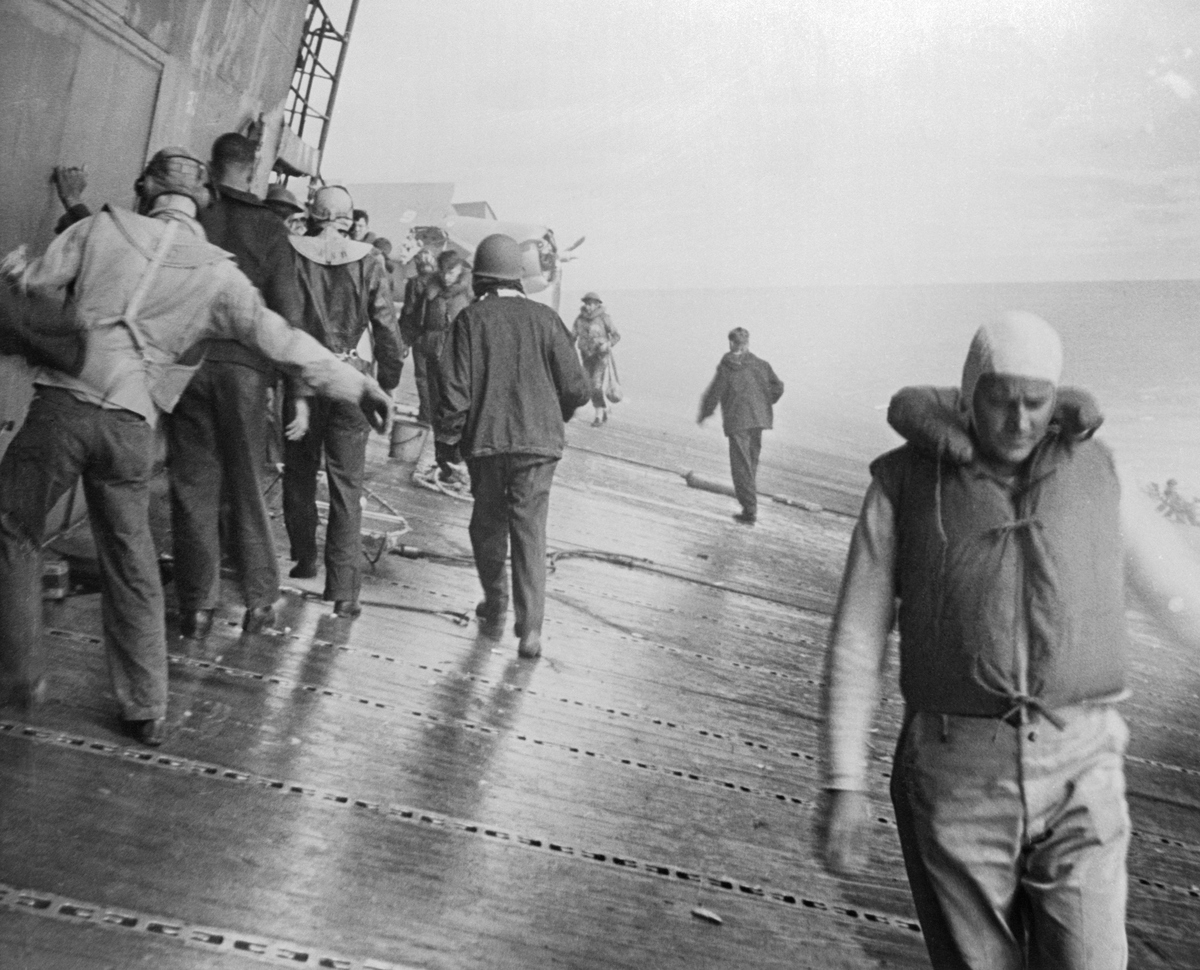Navy soldiers attend the U.S.S. Yorktown aircraft carrier listing badly after she had been hit by bombs and torpedoes in the Battle of Midway.