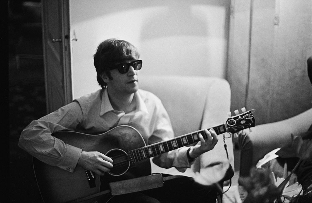 Lennon playing the guitar with sunglasses