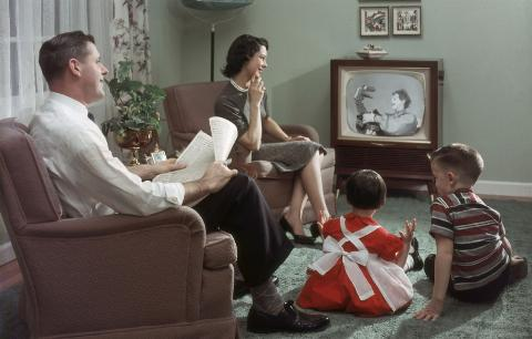 A happy family cheerfully sits in their living room and watches a televisied clown and puppet