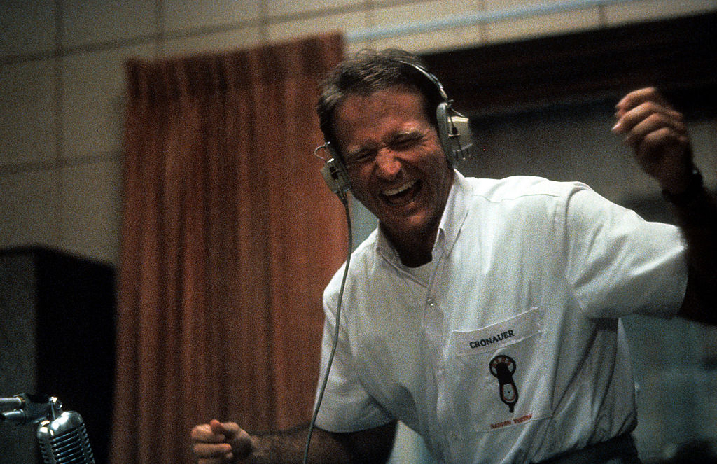 Robin Williams enjoying music through headset in a scene from the film 'Good Morning, Vietnam',