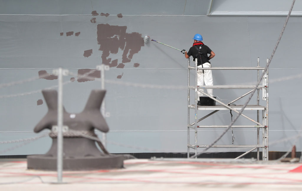 A contractor paints the side of HMS Queen Elizabeth