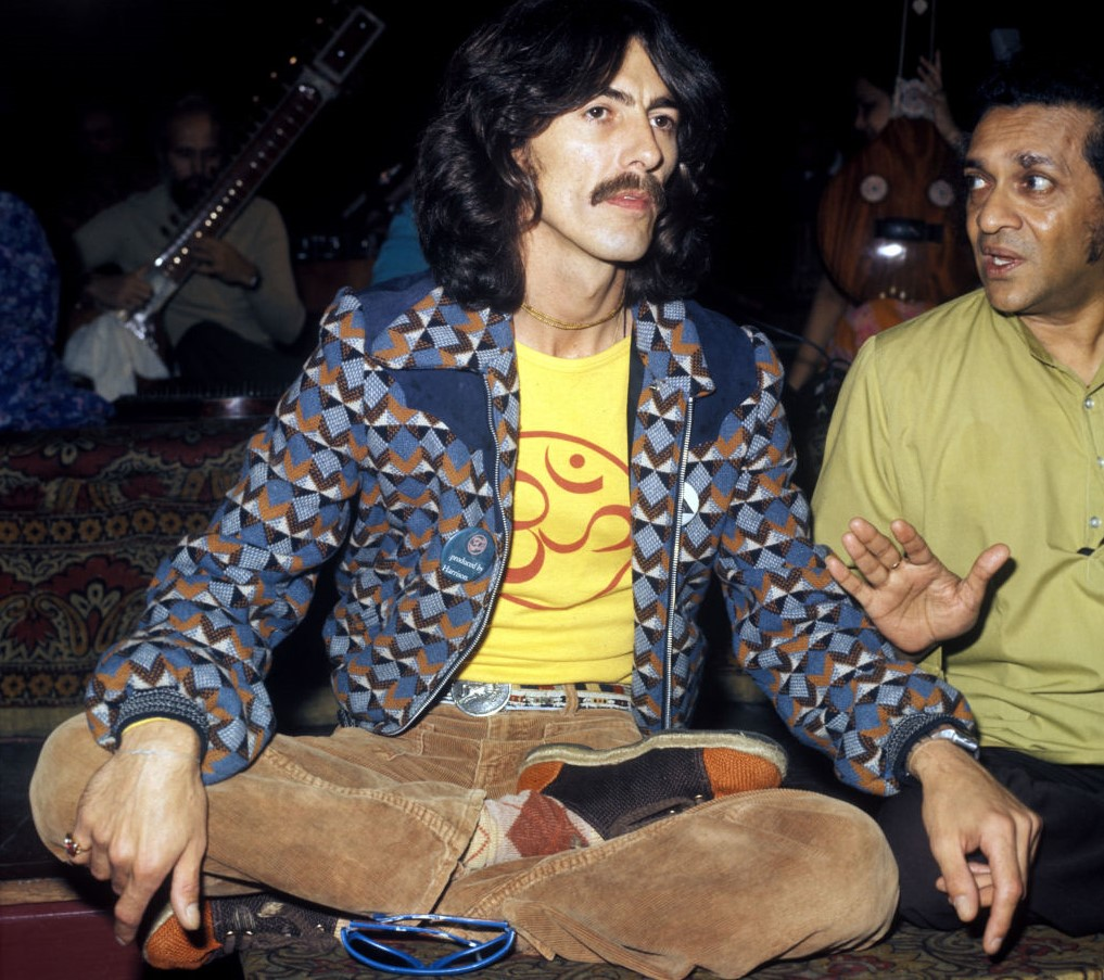 George Harrison wears a namaste shirt while sitting with his legs folded.