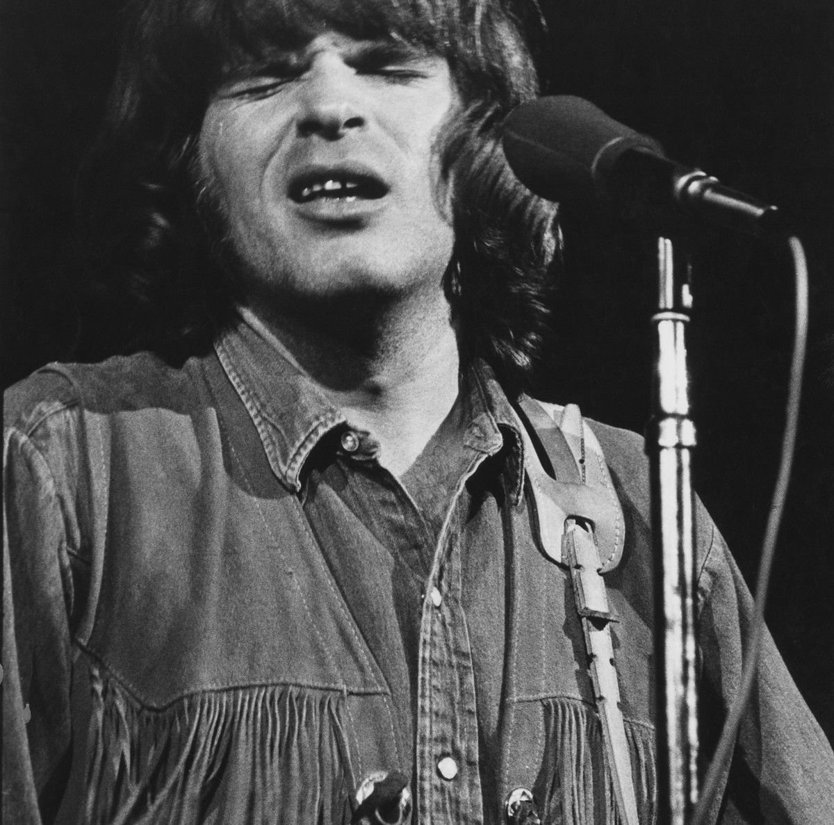 John Fogerty sings into a microphone onstage.