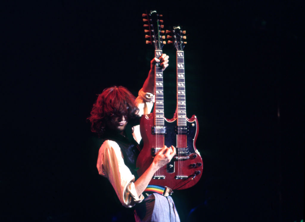 Jimmy Page plays a double-neck guitar onstage.