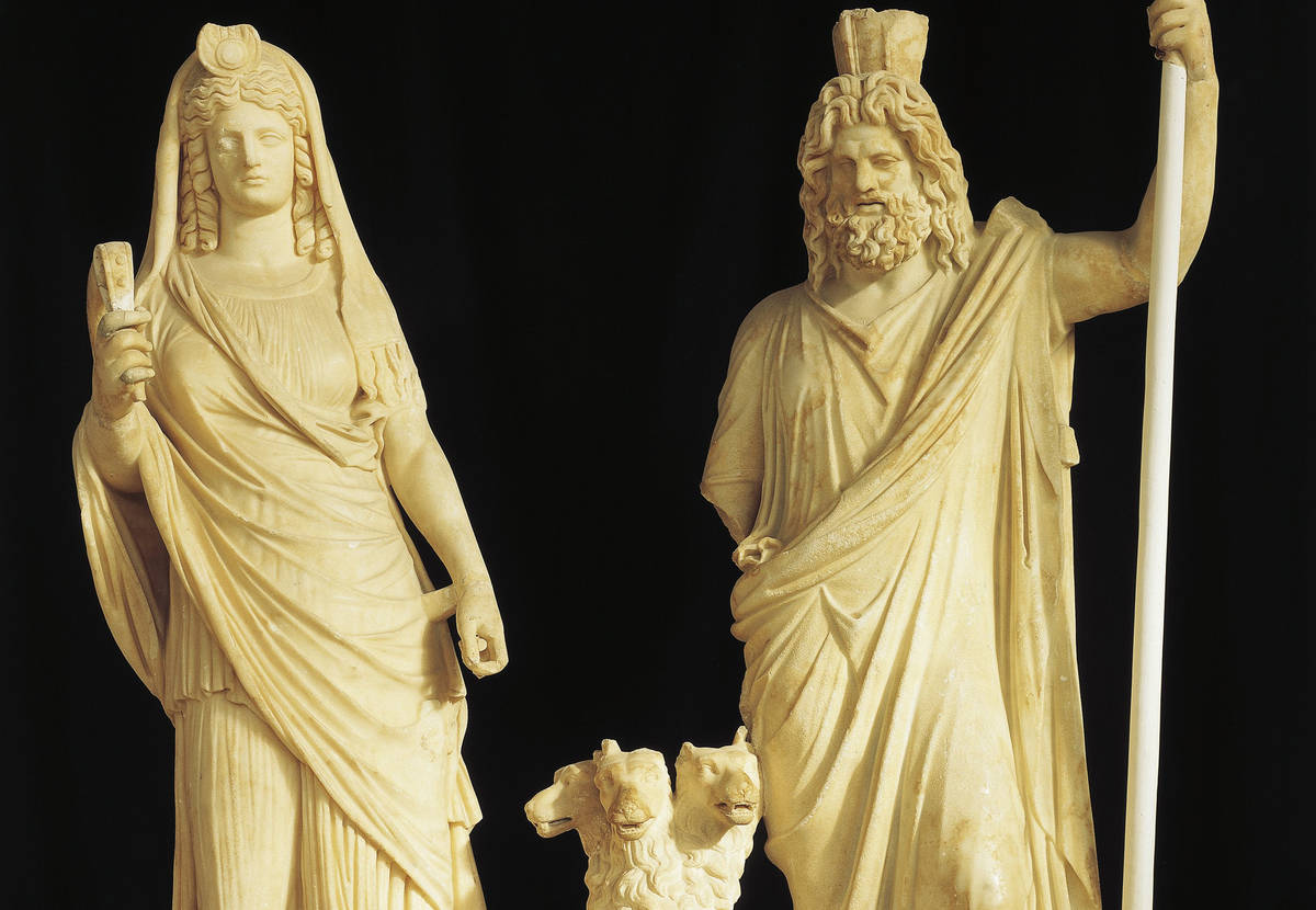 Statues of Hades (Pluto) and Persephone (Proserpine) with Cerberus are seen in a shrine.