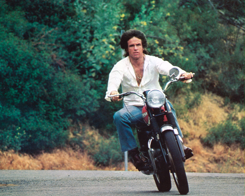 Warren Beatty drives a motorcycle near a hillside.