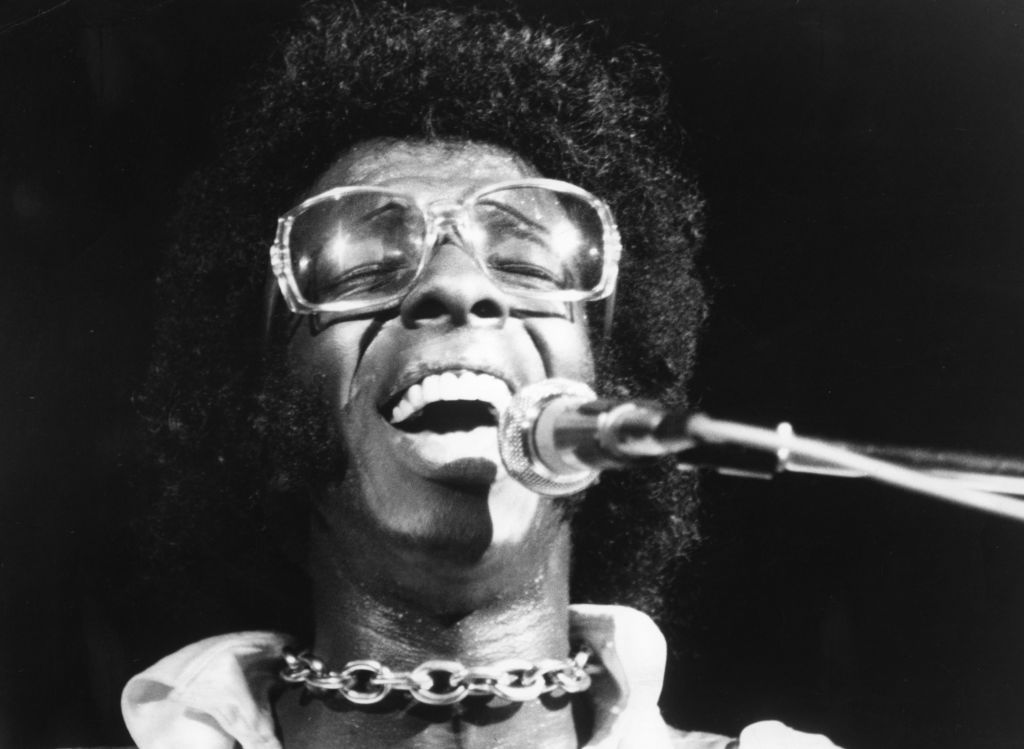 Sly Stone sings into a microphone.