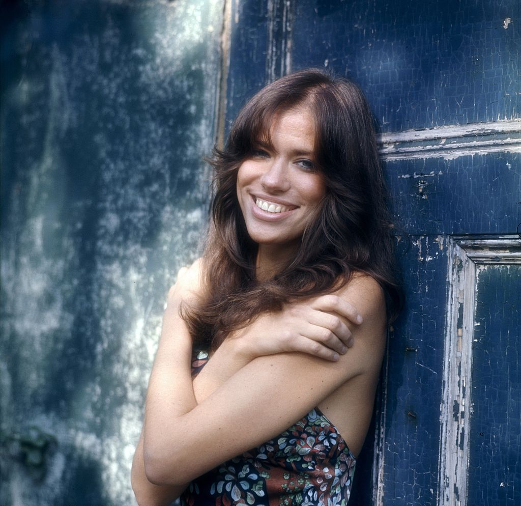 Carly Simon smiles in front of a blue door.