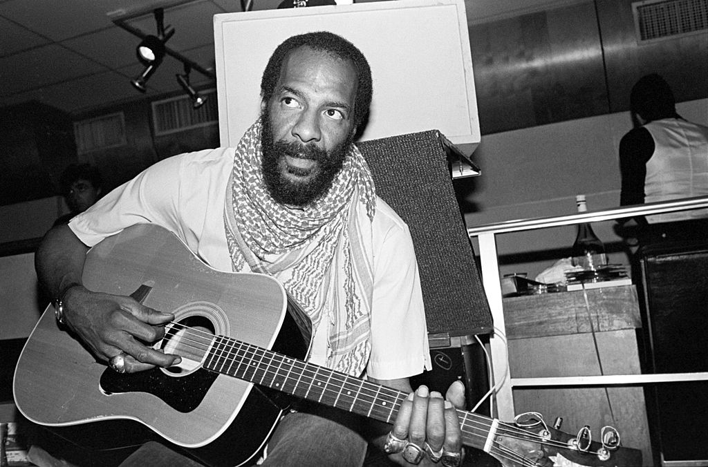 Richie Havens strums a guitar backstage.