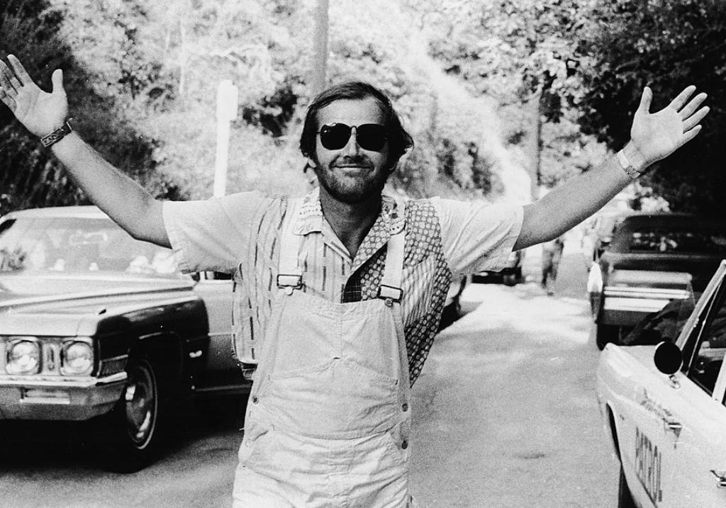 Jack Nicholson holds his arms out wide while walking through a parking lot surrounded by nature.