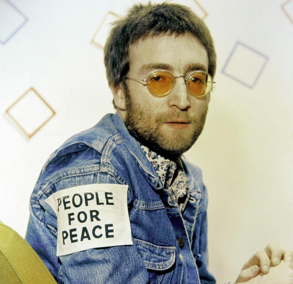 John Lennon wears orange, circular sunglasses and a jean jacket that reads