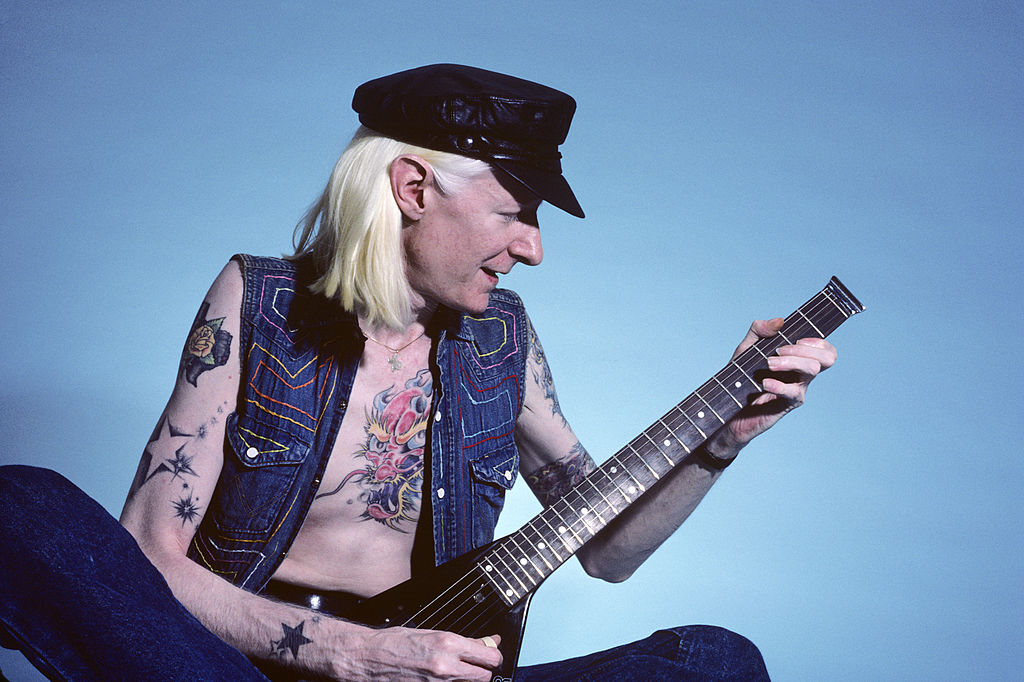 Johnny Winter plays his guitar in front of a blue backdrop during a photoshoot.
