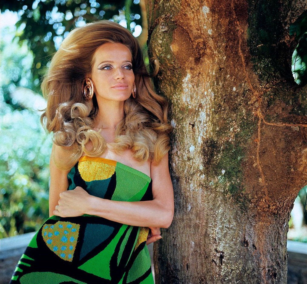 Veruschka von Lehndorff poses next to a tree.