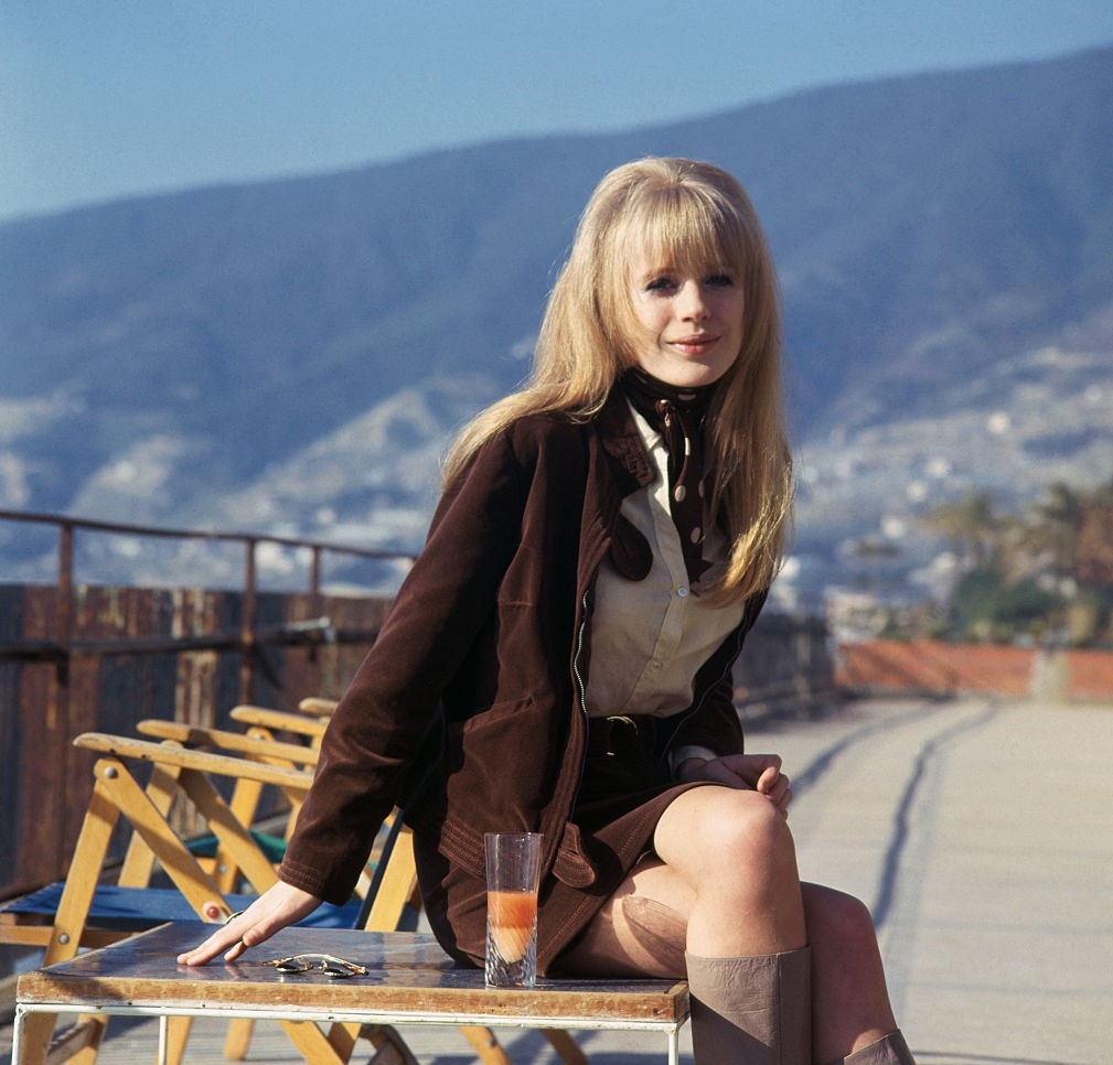 Marianna Faithfull poses outside in front of a hillside.