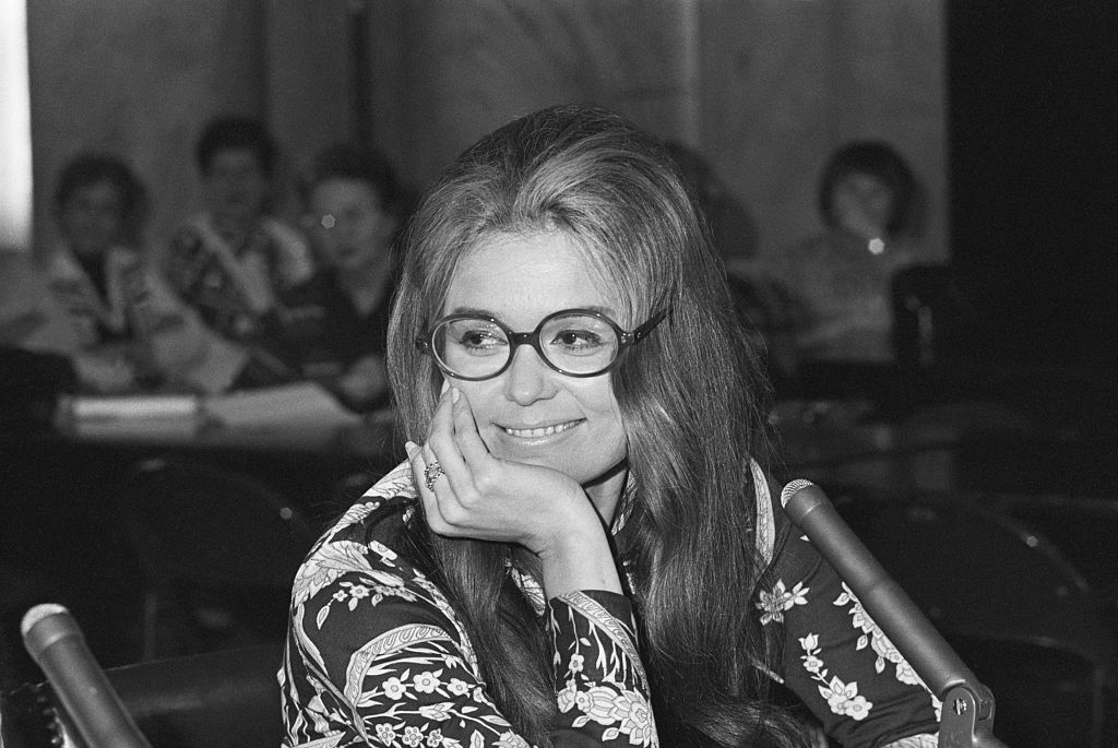 Gloria Steinem smiles at a press conference.