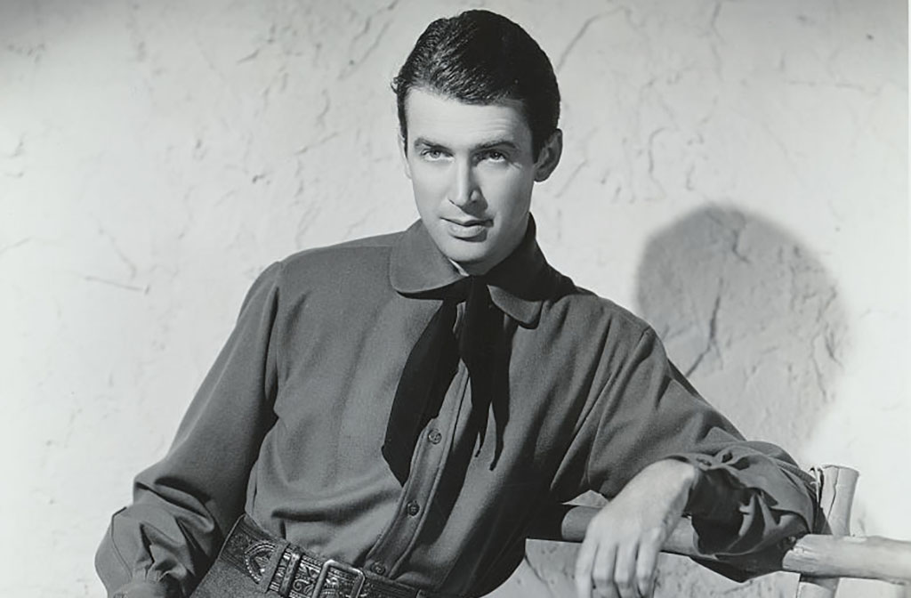 Jimmy Stewart leaning against a gate