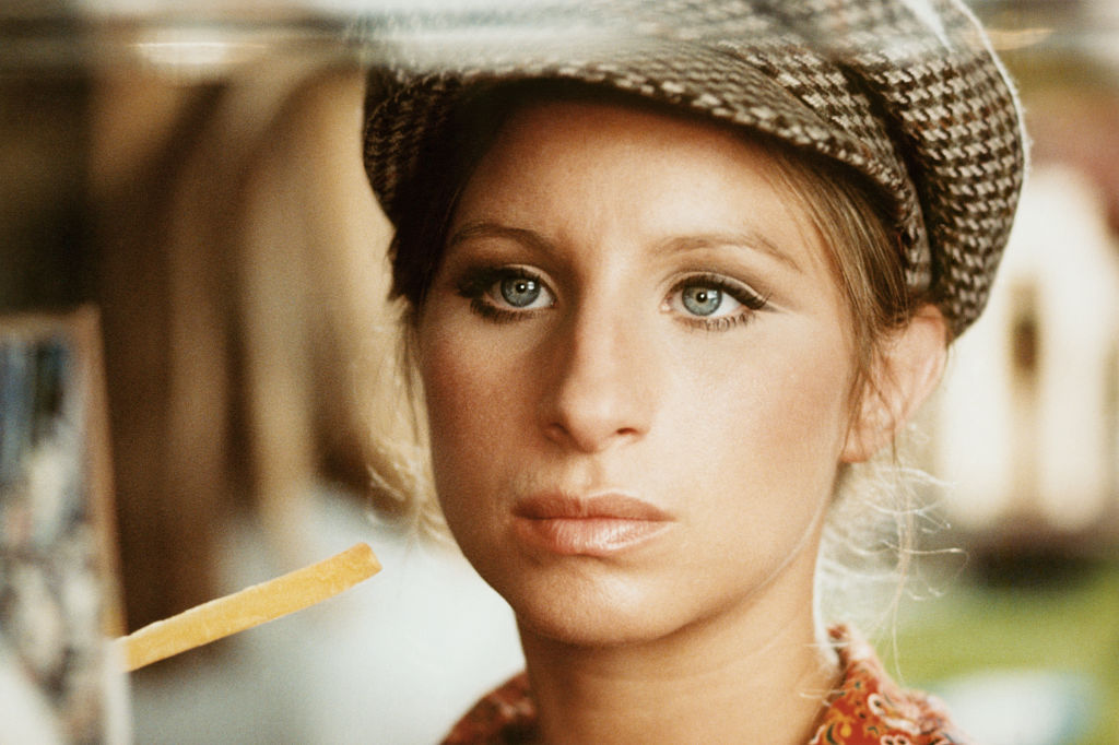 Barbra Streisand wears her hair tucked into a cap and a serious expression.