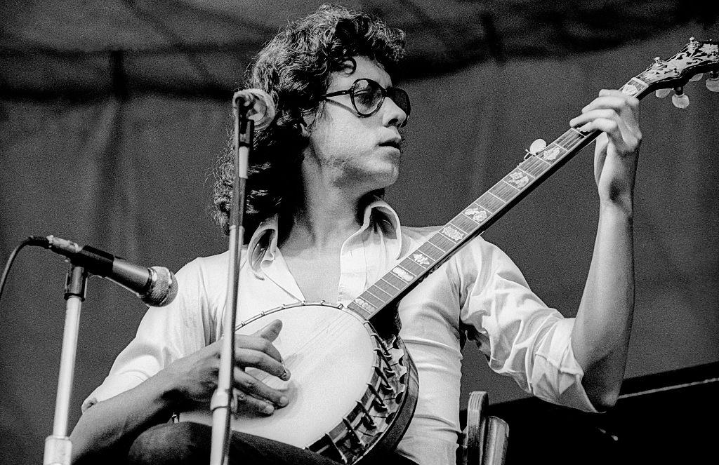 Arlo Guthrie plays a banjo onstage.