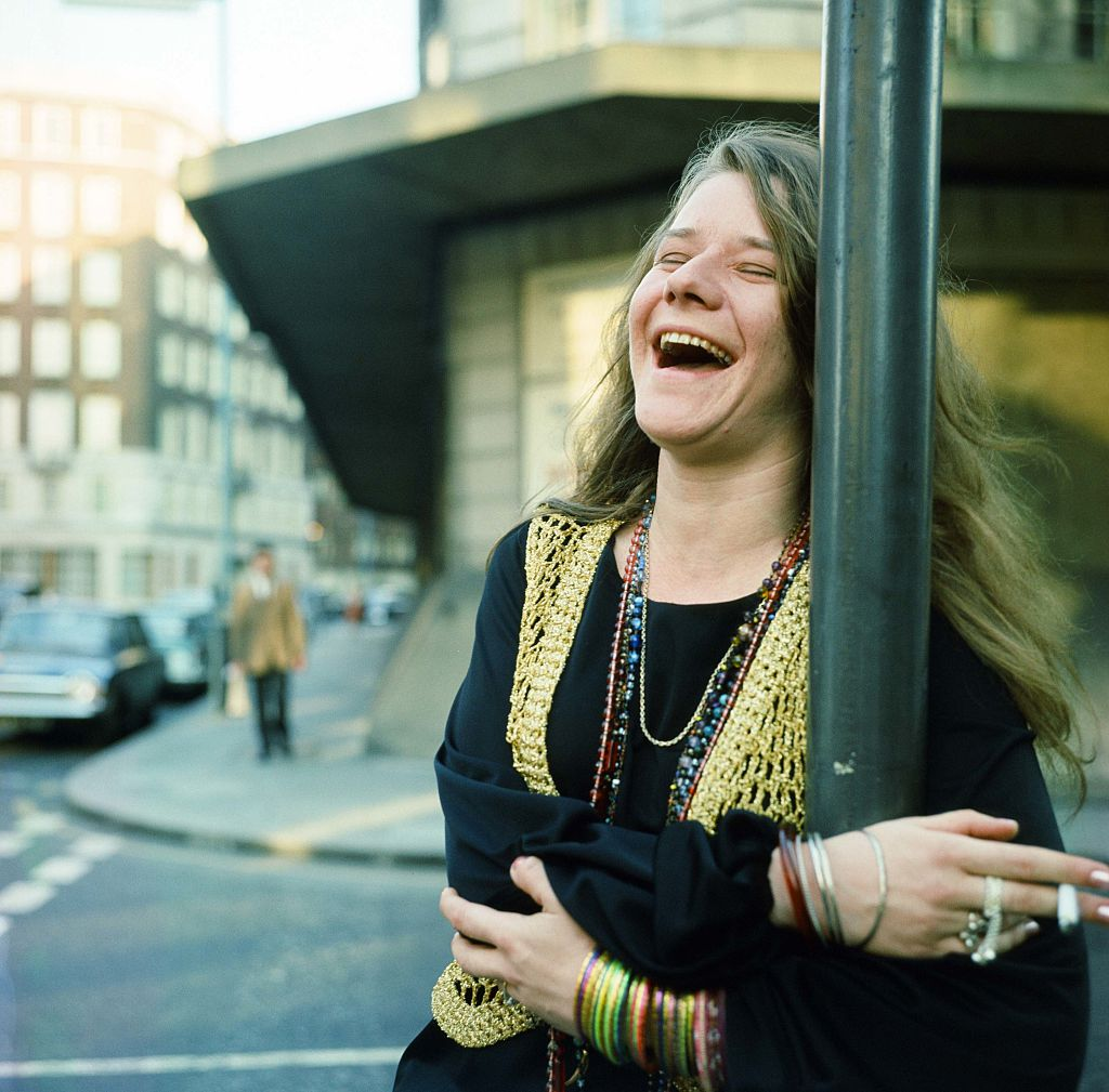 Janis Joplin laughs on a street corner.