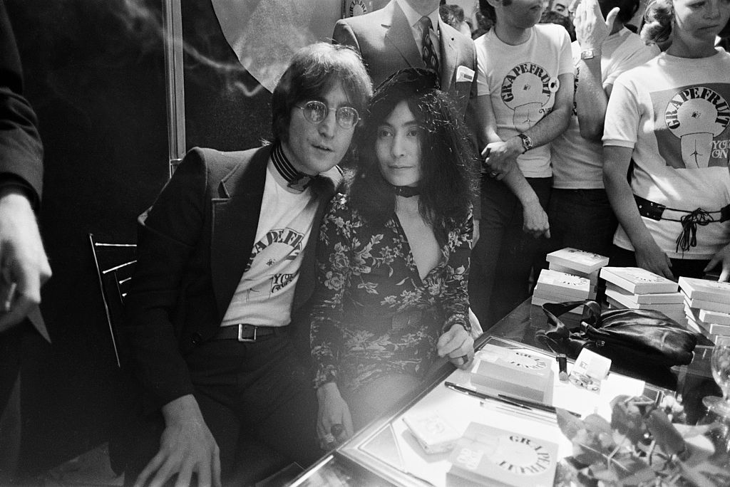 John Lennon and Yoko Ono sit in a crowd at a book signing.