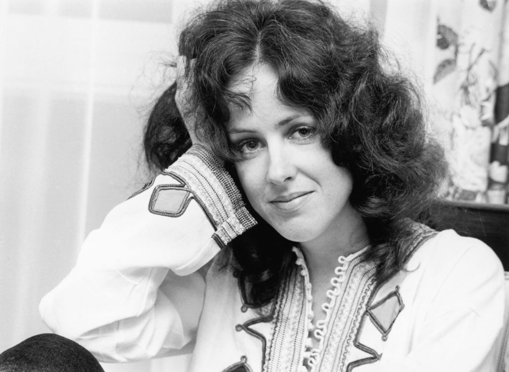 Grace Slick leans her head on her hand while sitting in a living room.