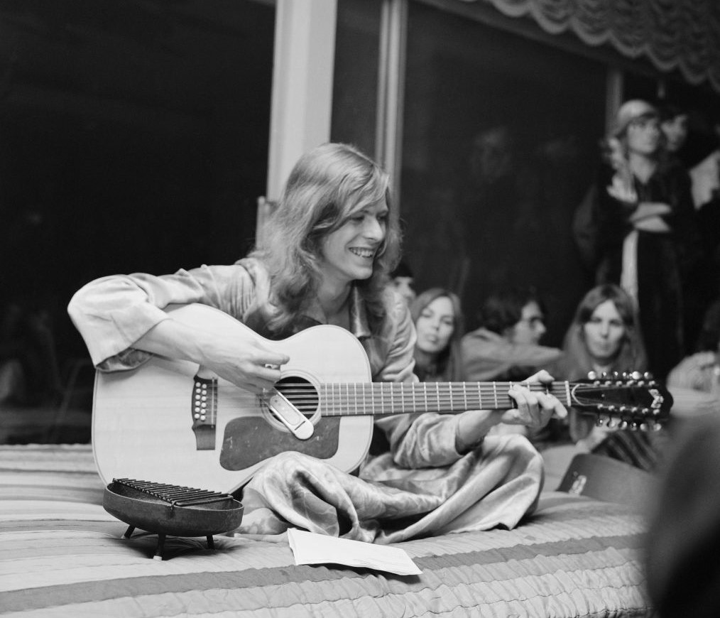 David Bowie plays guitar while sitting on a bed and surrounded by friends.