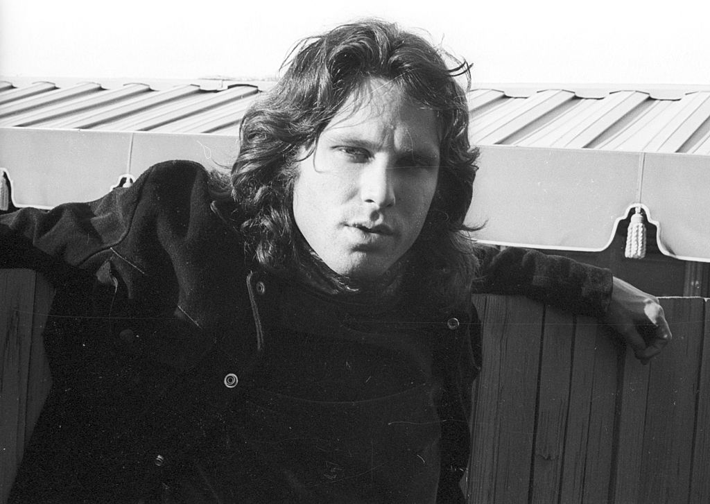 Jim Morrison poses next to a wooden fence.