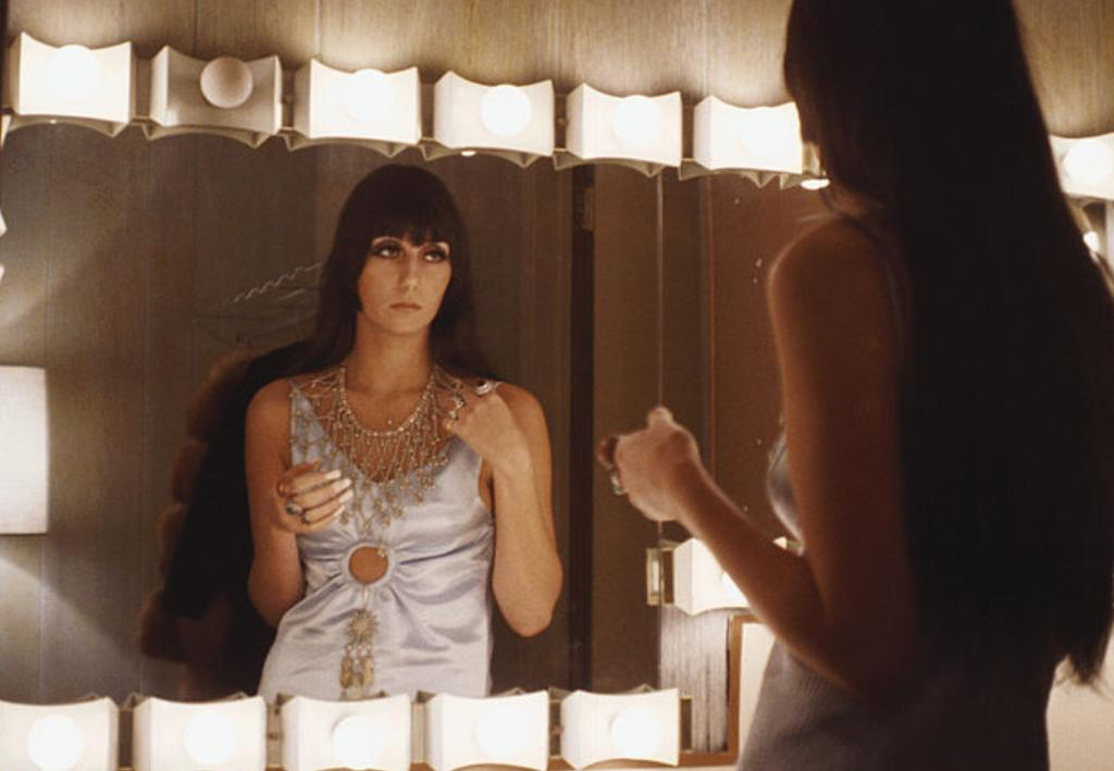 Cher looks into a dressing room mirror.