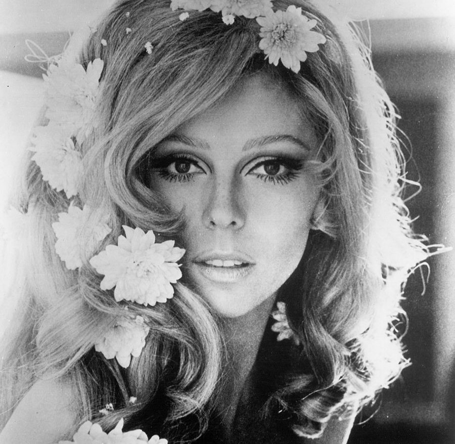 Nancy Sinatra wears flowers in her hair while looking into the camera.