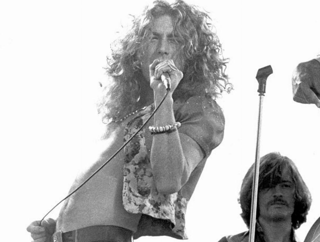 Robert Plant sings onstage.