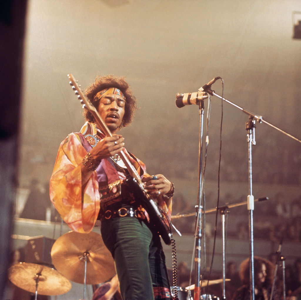 Jimi Hendrix plays guitar with his eyes closed onstage.