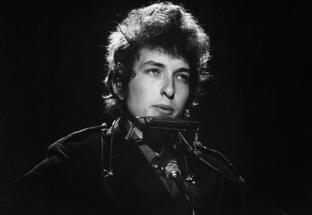 Bob Dylan plays guitar onstage.