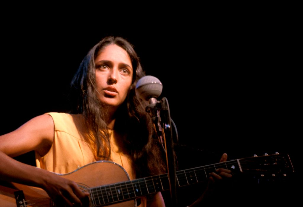 Joan Baez plays guitar onstage.