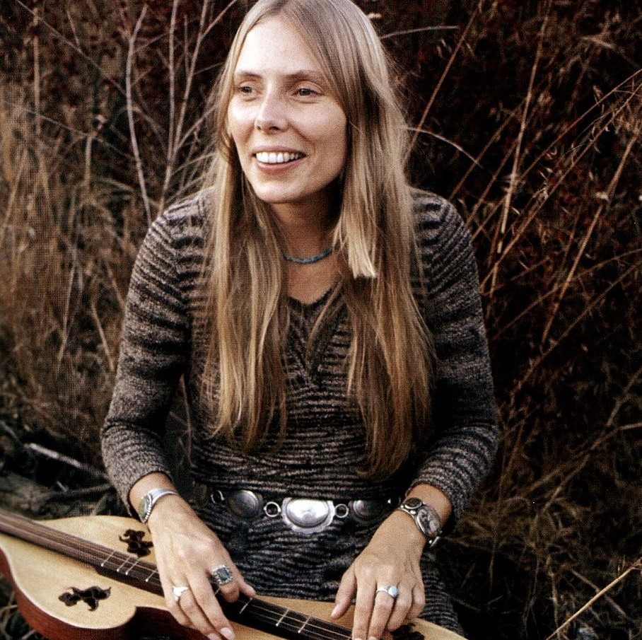 Joni Mitchell plucks strings of her instrument while sitting outside in nature.