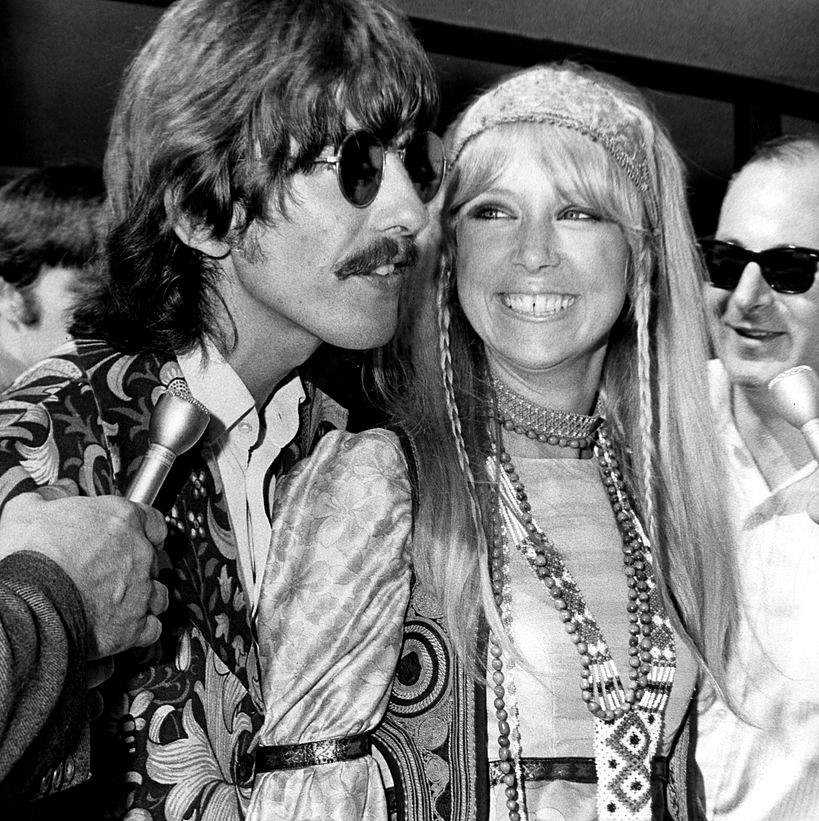Pattie Boyd is dressed in hippie attire and smiling at George Harrison amidst reporters.