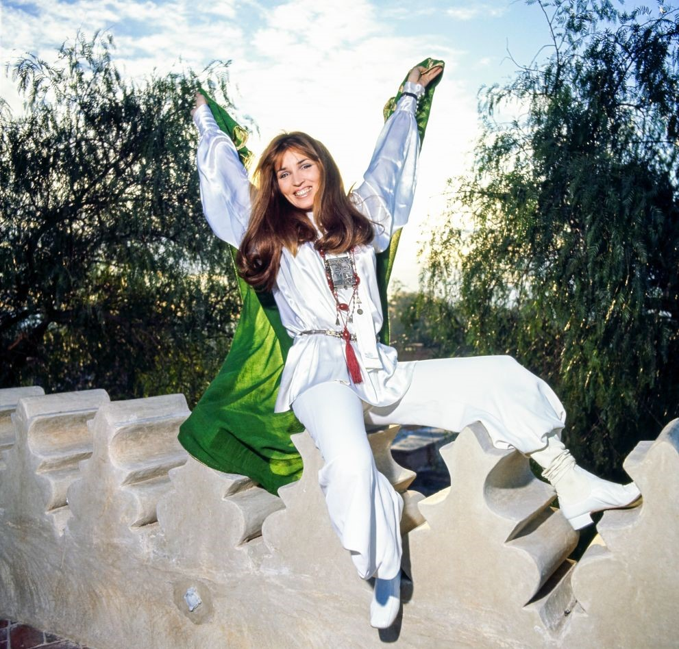 Talitha Getty holds out her arms while sitting on a rooftop.