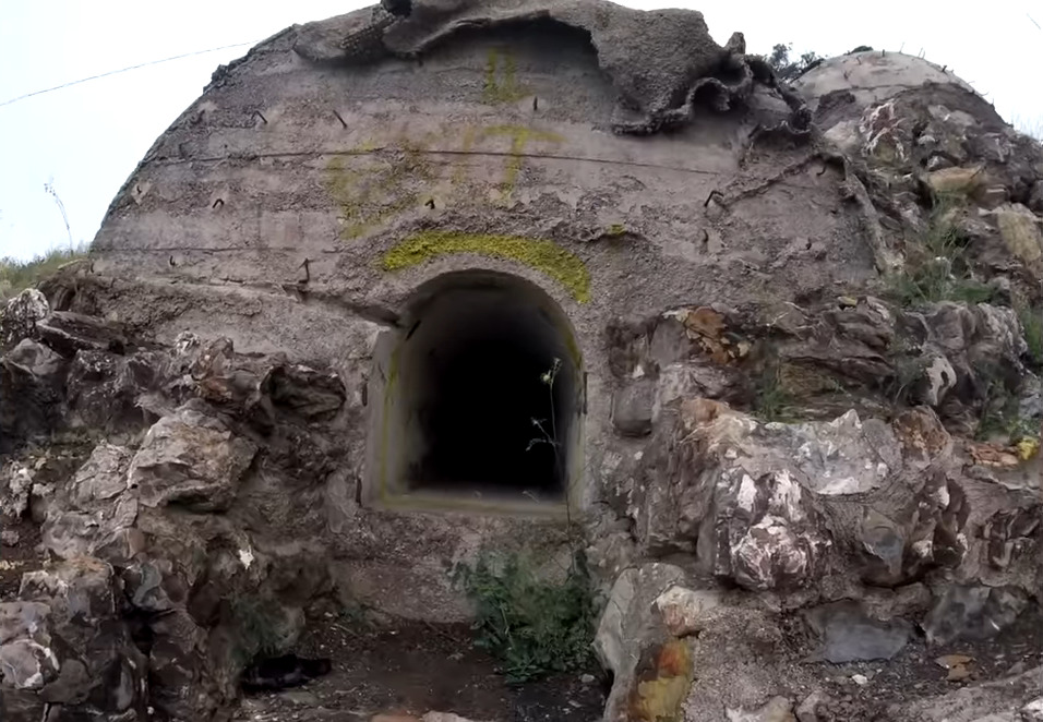 YouTubers film the entrance to the abandoned Monte Moro Bunker in Italy.