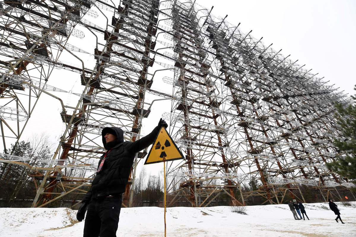 A visitor poses next to a sign with the radiation warning symbol in front of the construction of the Duga Radar.