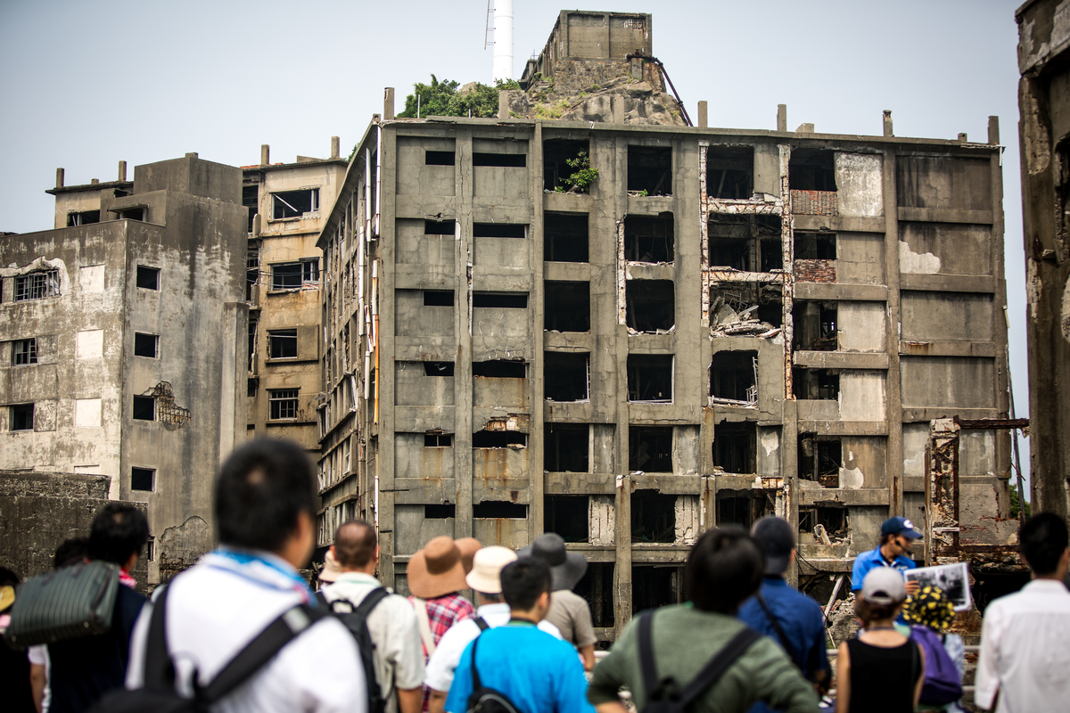 Tourists see abandoned buildings of Hashima Island.
