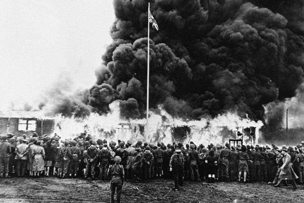 Allied soldiers watching a camp burn