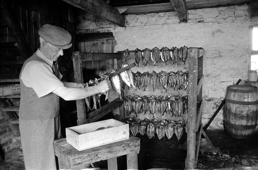 A fisherman hanging his catch on racks in preparation for salting