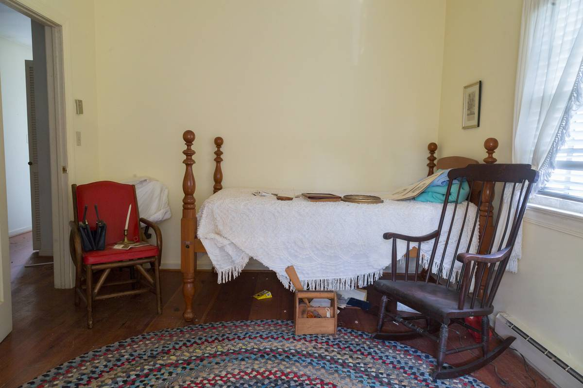 A room has a couple of chairs and a twin bed.