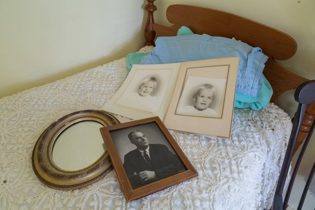 Resting on the twin bed are vintage photographs.