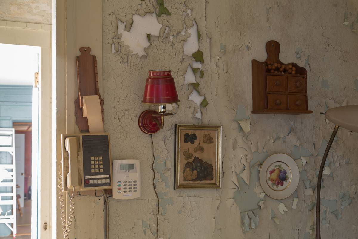 Items hang from a peeling wall.